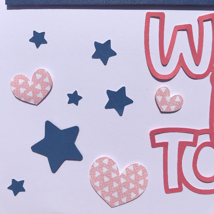 Adding stars and hearts to the family scrapbook page to finish it