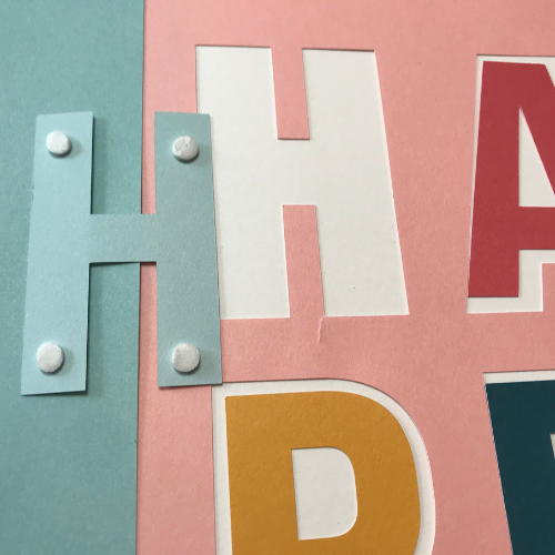 Use the 3D foam dots on happy for some depth on your Cricut scrapbook template